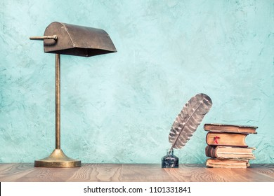 Quill ink pen with inkwell, aged books and retro brass lamp on wooden desk front aquamarine concrete wall background. Vintage old style filtered photography