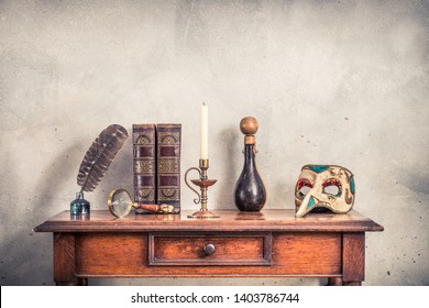 Quill ink pen with old inkwell, antique books, brass magnifying glass, candle in vintage candlestick, bottle covered with leather, carnival mask on oak wooden table. Retro style filtered photography