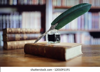 Quill pen and ink well resting on an old book in a library concept for literature, writing, author and history