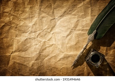 Quill pen and ink well resting on blank parchment paper background with copy space for message