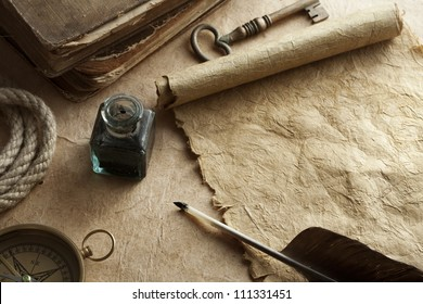 quill pen and inkwell on vintage paper background