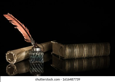 Quill pen and a rolled papyrus sheet on a wooden table with old books, vintage effect