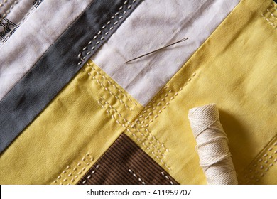 Quilted fabric layer in yellow, grey, white and black with thread and needle