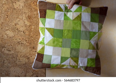 Quilted handmade cushion in Christmas colors green and brown with christmas star pattern behind the cork wall in the woman's hand