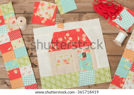 Quilted House. Sewing And Quilting Accessories. Fabric Patches. Wooden Table.
