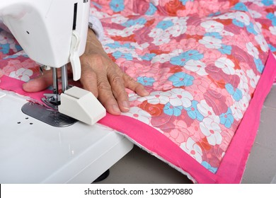 A quilter carefully guides binding material through a sewing machine to apply the final binding  to a new quilt.