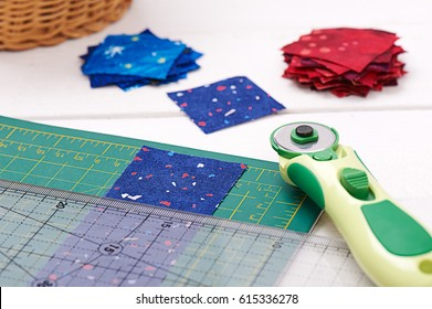 Quilting tools, piece of fabric prepared to cutting, two heaps cut off of fabrics