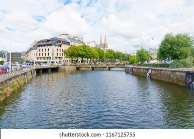 Quimper, France - August 8 2018: Looking down the Odet River as it flows through Quimper, people walk on tree lined banks, bordered by commercial buildings and parked cars.