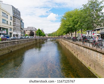 Quimper, France - August 8 2018: Looking down the Odet River flowing through Quimper between tree lined banks, bordered by commercial buildings and parked cars.