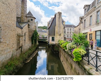 Quimper, France - August 8 2018: Tourists taking photogrpahs on the Rue de la Herse, looking down the River Steir flowing between old buildings towards the River Odet.