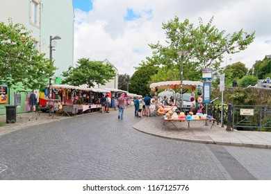 Quimper, France - August 8 2018: Shoppers and tourists wander through a small street market on the cobbled streets of Place Medard.