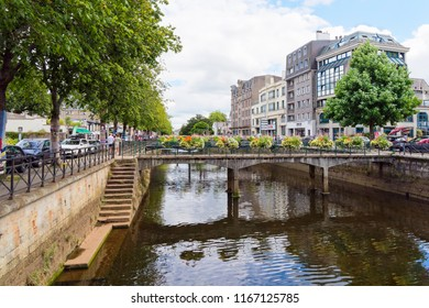 Quimper, France - August 8 2018: Looking down the Odet River flowing through Quimper, people walk on tree lined banks, bordered by commercial buildings and parked cars.