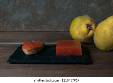 Quince cheese, quince toast and quince fruit on table.