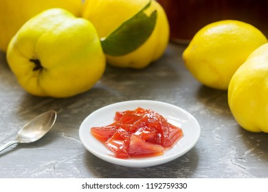 Quince jam on a white saucer, quince fruits and jars of jam on a gray background.
