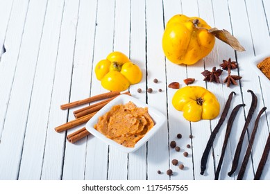 quince jelly and ingredients on white wooden table background