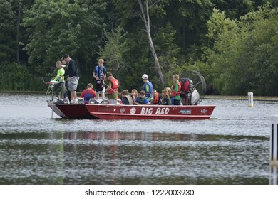 Quincy, Wisconsin / USA - July 25, 2013: An airboat full of people some doing bow and arrow fishing on a quiet bay along the Castle Rock Lake.