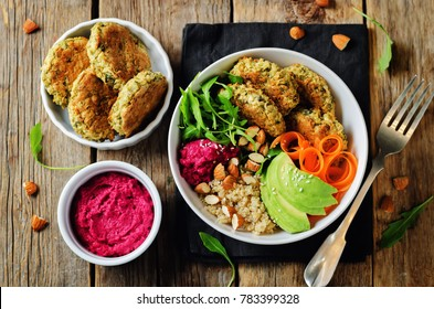 Quinoa Beet Hummus Falafel Bowl on a wood background. toning. selective focus