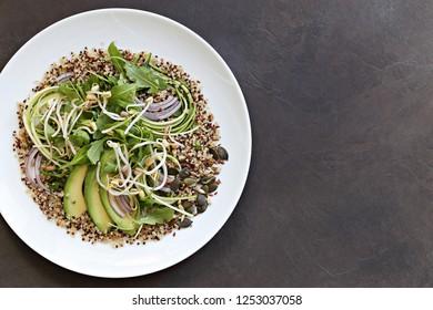 Quinoa detox salad with avocado, arugula, zucchini and seed mix. Plant based, clean eating, keto, super food.