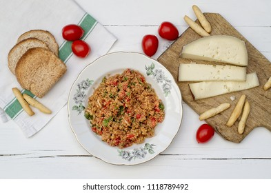 Quinoa dish with vegetable and cherry tomatoes, chopping board with slices of asiago cheese, sliced bread, bread sticks on white wooden table (top view)