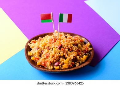 Quinoa dish with vegetable and cherry tomatoes, chopping board with slices of asiago cheese