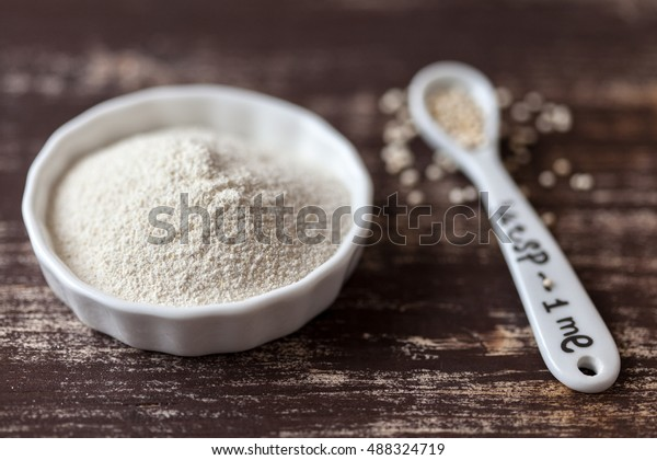 Quinoa flour on a dark wooden table with a tablespoon