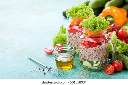 Quinoa and fresh vegetable salad in glass jars, selective focus