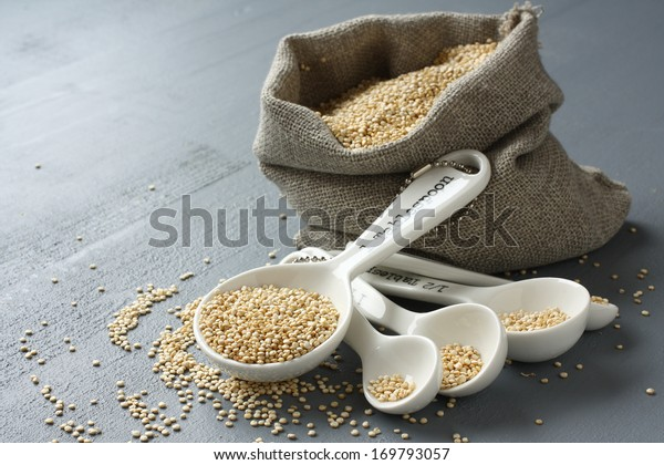 Quinoa grain in small burlap sack and porcelain measuring spoons on gray background