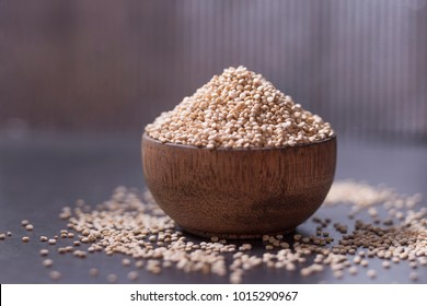 Quinoa grains in wooden bowl on black background