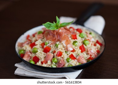 Quinoa with green peas, red sweet pepper and parma ham in a frying pan on a wooden background. Healthy superfood
