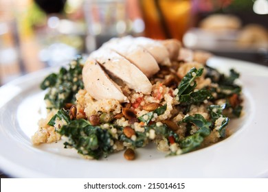 Quinoa and Kale Salad Topped with Sliced Chicken Breast