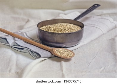 Quinoa in a pot and wooden spoon