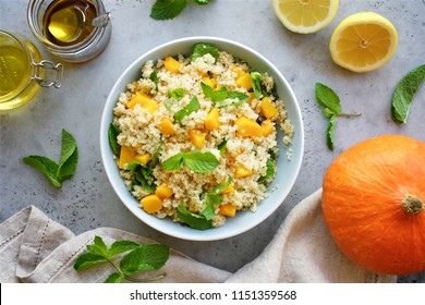 Quinoa salad with baked pumpkin and mint in bowl. Lemon honey dressing for salad. Healthy food concept