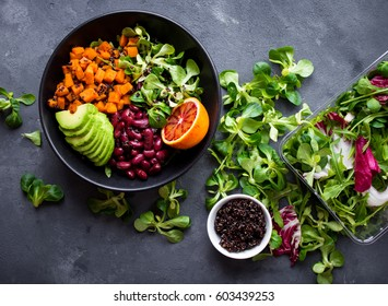 Quinoa salad in bowl with avocado, sweet potato, beans, herbs, orange on concrete rustic background. Quinoa superfood concept. Clean healthy detox eating. Vegan/vegetarian food. Making healthy salad