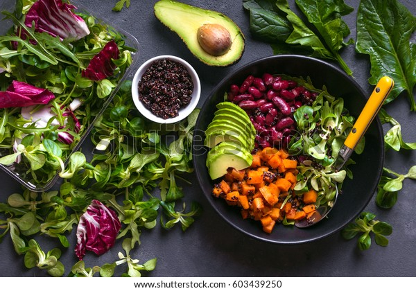 Quinoa salad in bowl with avocado, sweet potato, beans, herbs, spinat on concrete rustic background. Quinoa superfood concept. Clean healthy detox eating. Vegan/vegetarian food. Making healthy salad