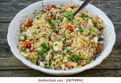Quinoa salad. Freshly made quinoa salad with heirloom tomatoes, mozzarella cheese, herbs and red onions in white serving bowl.