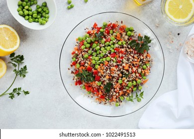 Quinoa salad with green peas, carrot, paprika and greenery. Spring detox salad with quinoa and fresh vegetables. Super food and clean eating concept ingredients.