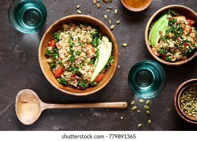 Quinoa salad with kale, cherry tomatoes and pumpkin seeds. Top view, dark wooden background