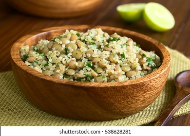 Quinoa salad with lentils and parsley in wooden bowl, photographed on dark wood with natural light (Selective Focus, Focus one third into the salad)