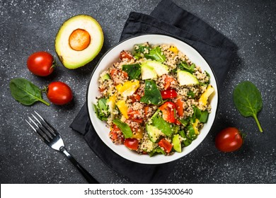 Quinoa salad with spinach, avocado, paprika and tomatoes on black stone table. Top view.