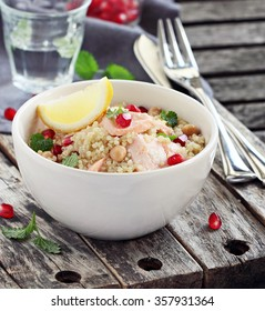 Quinoa salad with steamed salmon,chickpea,pomegranate and mint on a rustic wooden table. Superfoods concept