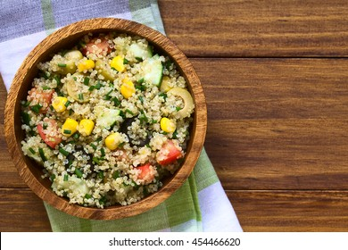 Quinoa salad with sweet corn, olive, tomato, cucumber and chives in wooden bowl, photographed overhead on dark wood with natural light (Selective Focus, Focus on the top of the salad)
