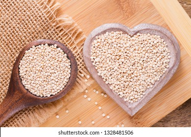 Quinoa seeds in bowl on rustic wood.