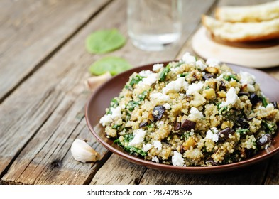 quinoa spinach eggplant feta salad on a dark wood background. the toning. selective focus
