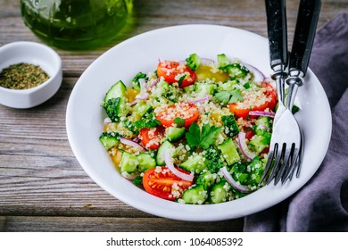 Quinoa Tabbouleh salad bowl with cucumbers, tomatoes, red onions and parsley on wooden background