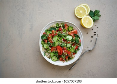 Quinoa tabbouleh salad. Cucumbers, bell peppers, tomatoes, parsley, onions, mint ingredients