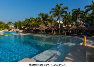 QUINTANA ROO, MEXICO - SEPTEMBER 16, 2018: Outdoor pool in hotel and resort with coconut palms and chairs around