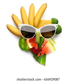 Quirky food concept of cubist style female face in sunglasses made of fruits and vegetables, on white background.