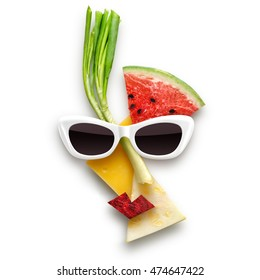 Quirky food concept of female face in sunglasses made of fruits and vegetables, isolated on white.