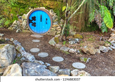 Quirky Garden Decoration of a Little Round Door, Like a Miniature Hobbit Hole, With a Stepping Stone Path Leading to It