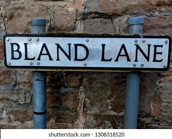Quirky road sign for Bland Lane, against a traditional stone wall in Epperstone, UK